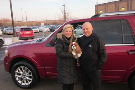 Couple in front of a red suv